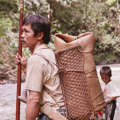 Local Penan man crossing a river