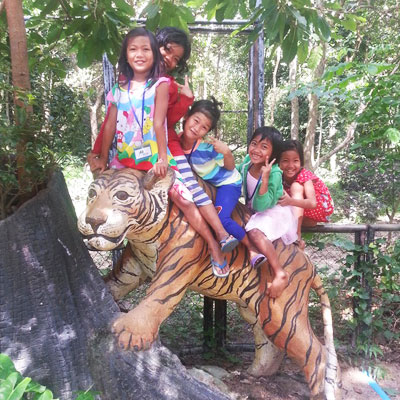 Children sitting on tiger statue