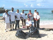 Beach cleaning at Smith Cove, Cayman Islands. Photo by Cayman Islands Tourist Board